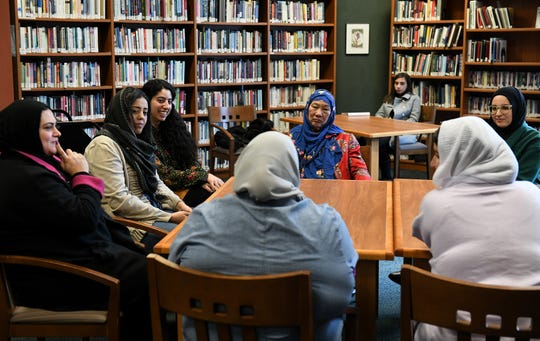 From left, Machhadie Assi of Dearborn, Masha Almulaiki of Highland Park, Lujine Nasralla of Detroit, Weihan Hi of Farmington Hills, Baraa Ktiri and Mariam Ktiri of Farmington Hills, in white, during a discussion about hijab facilitated by artist in residence Baraa Ktiri at the Arab American National Museum library in Dearborn, Mich. on Jan. 26, 2020.