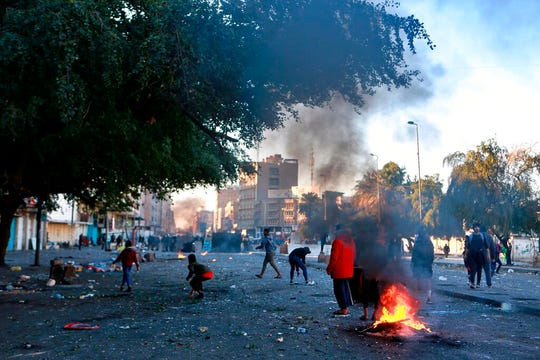 Protesters set fire to close a street during clashes between security forces and anti-government protesters near Baghdad's Khilani square, Iraq, Sunday, Jan. 26, 2020.