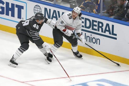 Detroit Red Wings forward Tyler Bertuzzi tries to pass around San Jose Sharks forward Tomas Hertl.