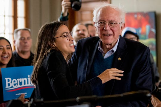 Democratic presidential candidate Sen. Bernie Sanders, I-Vt., smiles as he is welcomed to the podium by Rep. Alexandria Ocasio-Cortez, D-N.Y., left, at a campaign stop at La Poste, Sunday, Jan. 26, 2020, in Perry, Iowa.