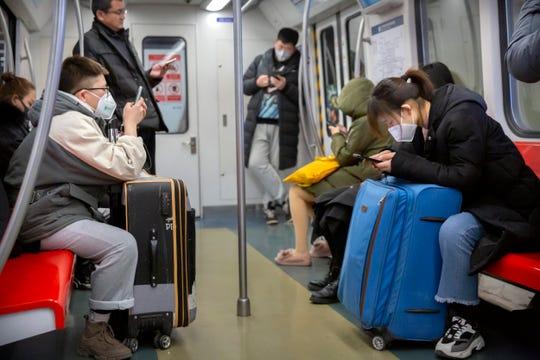 People wearing face masks ride a subway train in Beijing, Sunday, Jan. 26, 2020.