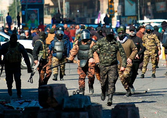 Security forces try to disperse anti-government protesters during clashes in Baghdad, Iraq, Sunday, Jan. 26, 2020.