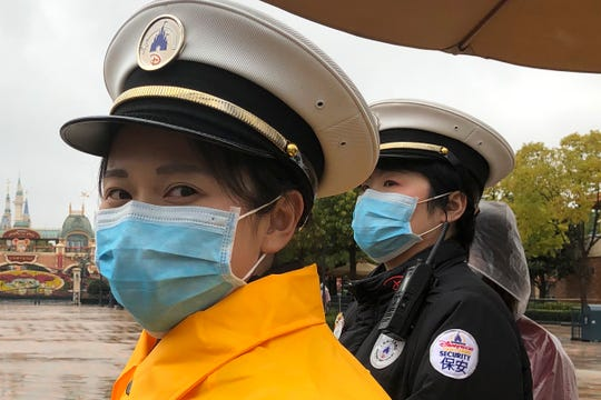 Security personnel wear face masks as they stand at the gates of the Shanghai Disney Resort, which announced that it will be closed indefinitely from Saturday, in Shanghai, Saturday, Jan. 25, 2020.