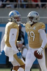 Cowboys receiver Amari Cooper (19) celebrates his touchdown with Lions receiver Kenny Golladay, left, during the first half on Sunday.