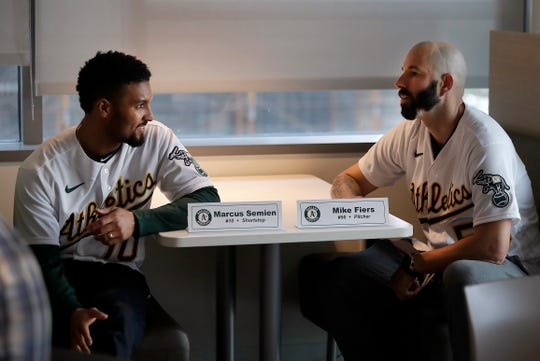 Athletics pitcher Mike Fiers, right, speaks with shortstop Marcus Semien prior to an interview.