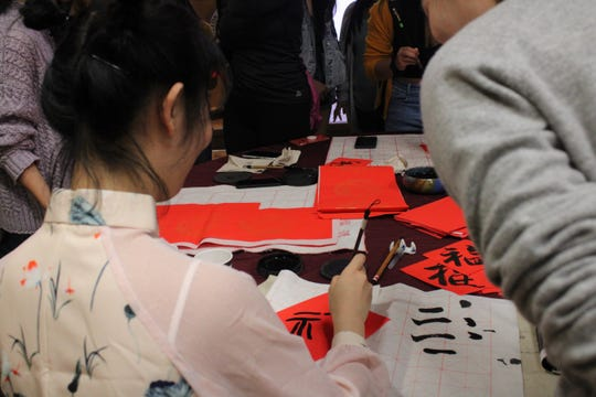 A Chinese student teaches attendees how to write calligraphy.