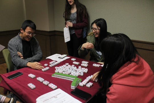 Students play the traditional Chinese game of Mahjong while enjoying the festivities of the new year celebration.