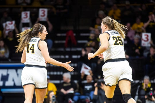 Iowa's McKenna Warnock (14) high-fives center Monika Czinano (25) after making a 3-point basket during the Hawkeyes' game Sunday against Michigan State at Carver-Hawkeye Arena in Iowa City.
