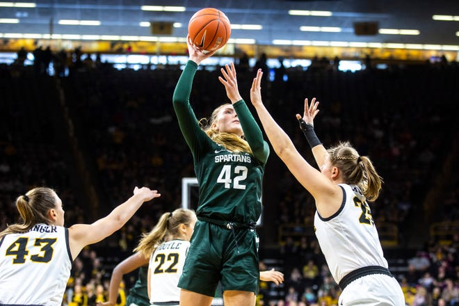 Michigan State forward Kayla Belles (42) drives to the basket as Iowa forward Amanda Ollinger (43) and center Monika Czinano (25) defend during a NCAA Big Ten Conference women's basketball game, Sunday, Jan. 26, 2020, at Carver-Hawkeye Arena in Iowa City, Iowa.