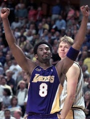 Los Angeles Lakers guard Kobe Bryant reacts as the Lakers win game four of the NBA Finals in overtime 120 -118 against the Indiana Pacers in Indianapolis Wednesday June 14 2000. Pacers center Rik Smits looks on in the background.