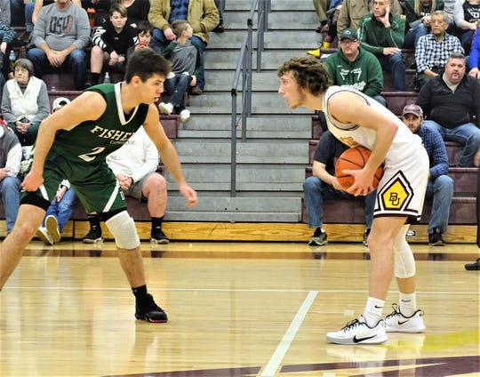 Fisher Catholic's Kaden Starcher guards Berne Union's Chase McCartney during the Rockets' 57-42 victory Saturday night.