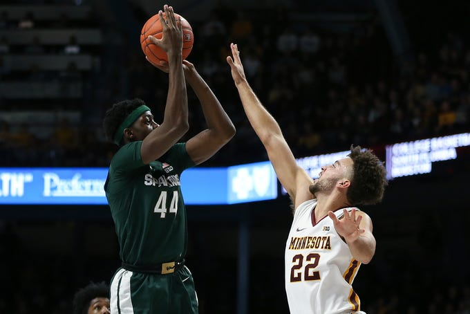 Michigan State's Gabe Brown, left, shoots against Minnesota's Gabe Kalscheur during an NCAA college basketball game Sunday, Jan. 26, 2020, in Minneapolis. (AP Photo/Stacy Bengs)