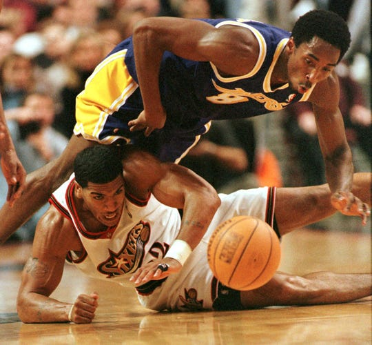 The Los Angeles Lakers' Kobe Bryant (top) flips over the Philadelphia 76'ers Jim Jackson as the two struggle for the loose rebound during their game 28 November in Philadelphia, PA.  The 76'ers won 105-95.