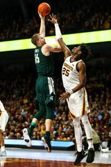 MSU's Thomas Kithier makes a jump hook over Minnesota's Daniel Oturu during Sunday's game in Minneapolis.
