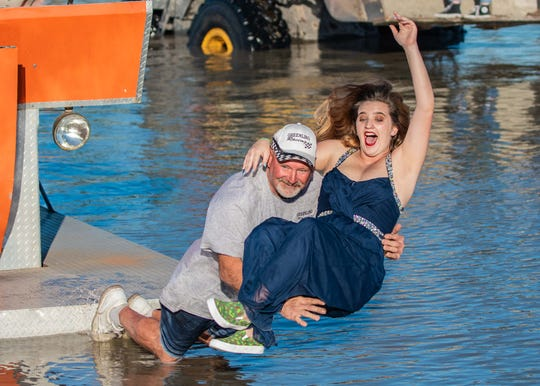 Dan Greenling celebrates winning the Big Feature by jumping into the sippy hole with Swamp Buggy Queen Courtney Mee on Jan. 26. Greenling won his third-straight Big Feature in his swamp buggy, Roll On.