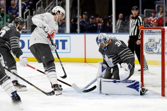New Jersey Devils forward Nico Hischier, center, scores a goal against Toronto Maple Leafs goalie Frederik Andersen (31) in the NHL hockey All Star game Saturday, Jan. 25, 2020, in St. Louis.