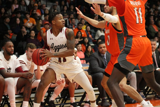 Evan Gilyard II, left, looks for the open man as two defenders close in during New Mexico State's road test against UTRGV on Saturday, Jan. 25, in Edinburg, Texas.