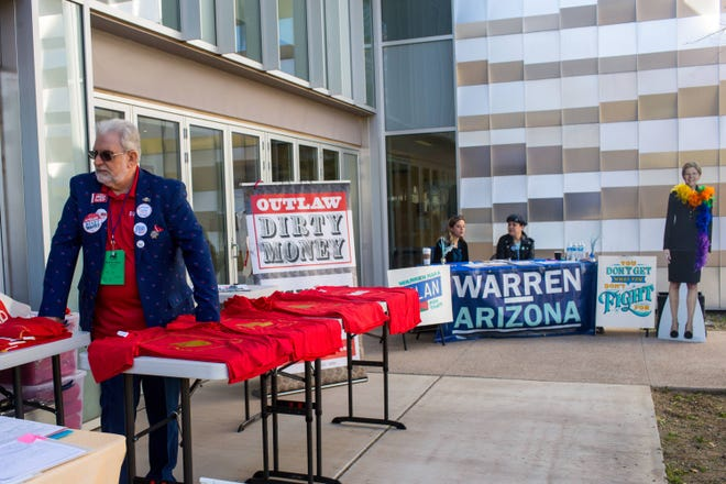 Marshall Militano sells shirts at an Outlaw Dirty Money booth during the Arizona Democratic Party State Committee meeting Saturday, Jan. 25, 2020 at Arizona Western College in Yuma.