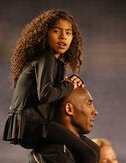Gianna Maria-Onore Bryant sits on the shoulders of her father, Kobe, as they attend the women's soccer match between the United States and China Thursday, April 10, 2014, in San Diego. Bryant, the 18-time NBA All-Star who won five championships and became one of the greatest basketball players of his generation during a 20-year career with the Los Angeles Lakers, died in a helicopter crash Sunday, Jan. 26, 2020. Gianna also died in the crash.