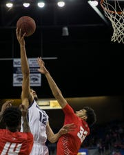Nevada  forward Johncarlos Reyes (12)) shoots over New Mexico forward Jordan Arroyo (33) during the second half of a basketball game played at Lawlor Events Center in Reno, on Saturday.
