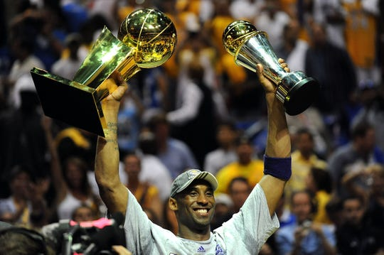 ORLANDO, FL - JUNE 14: Kobe Bryant #24 of the Los Angeles Lakers holds up the Larry O'Brien trophy and the MVP trophy after the Lakers defeated the Orlando Magic 99-86 in Game Five of the 2009 NBA Finals on June 14, 2009 at Amway Arena in Orlando, Florida. (Photo by Ronald Martinez/Getty Images)
