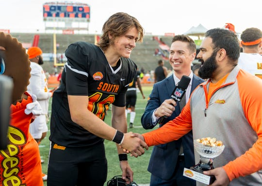 South quarterback Justin Herbert of Oregon (10) is given the MVP trophy after the 2020 Senior Bowl college football game at Ladd-Peebles Stadium.