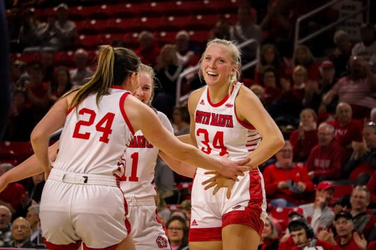 South Dakota's Hannah Sjerven (34) celebrates with Ciara Duffy (24) and Monica Arens (11) during the Coyotes' game against Oral Roberts on Jan. 26, 2020.