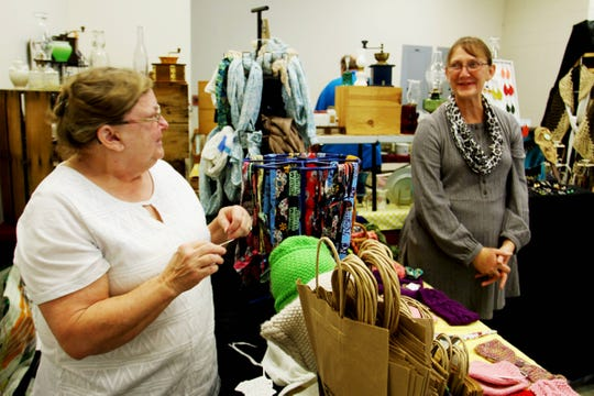 Cousins Anita Beard and Teri Rakes reminisce about when they first became vendors during the Greater Springfield Garage Sale & Marketplace Sunday at the Ozark Empire Fairgrounds.