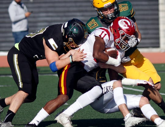 Oxnard High's Xavier Harris is taken down by a trio of East defenders during the West's 42-26 win at the 47th annual Ventura County All-Star Football Game on Saturday at Ventura College. Harris had 128 yards from scrimmage to earn West Offensive Player of the Game honors.