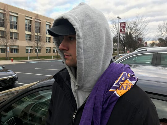 Bailey Ramirez, of Rahway, NJ, student at St. Joe's University leans against his car outside of Lower Merion High School with a Lakers shirt. He said he came here to pay his respects.