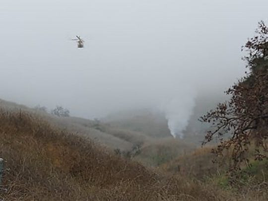 A helicopter flies over the scene of an aircraft crash in Calabasas, California on Jan. 26, 2020.