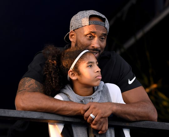 Kobe Bryant and daughter Gianna Bryant watch during day 2 of the Phillips 66 National Swimming Championships at the Woollett Aquatics Center on July 26, 2018 in Irvine, California.