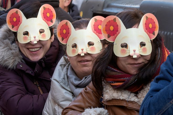 Spectators wearing Rat masks watch the parade during the celebrations for the Chinese New Year in the Usera district of Madrid, Spain on Jan. 26, 2020. Chinese worldwide are celebrating as they welcome the Year of the Rat.