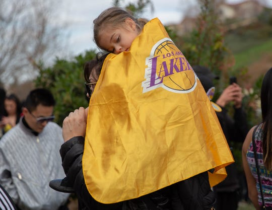 Jan 26, 2020; Calabasas, California, USA;  Valentina Martinez rests on her mother Janet Perez at the scene near a helicopter crash where former NBA star, Kobe Bryant is seen in Calabasas, Calif on Jan. 26, 2020. Bryant was one of nine people killed.  Mandatory Credit: Allison Zaucha-USA TODAY