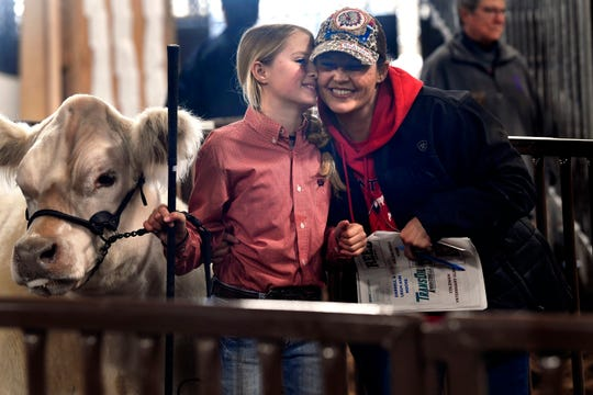 Fawn Gotcher leans in close to her daughter Steely as she is about to lead her Reserve Champion English Steer into the sale ring,