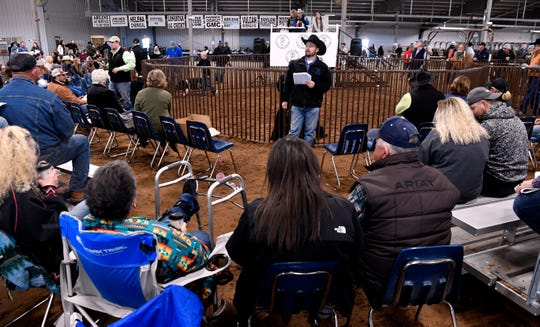 Audience members listen to the bids on a project at Saturday's sale.