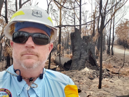 Michael Williams, a Nantahala National Forest senior firefighter, stands by the remains of a bushfire in New South Wales, Australia, where he is serving a month-long deployment.
