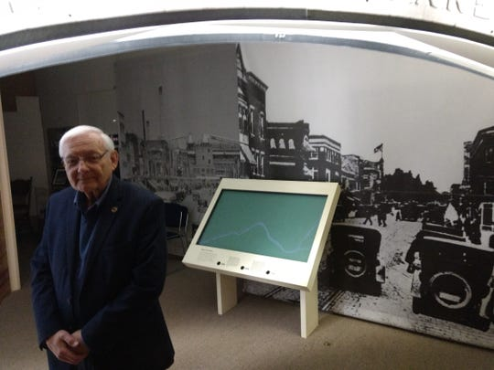 Mike Vanuga under a replica of the Home of the Square Deal arch at the Endicott Visitor Center. He serves as the center's photographer.