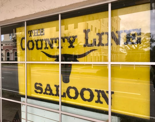 A yellow County Line Saloon sign faces Strawbridge Avenue traffic from the window of the former Grimaldi Candies building.