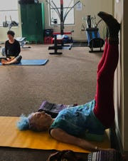Class members are invited to use the space freely and as they need at the beginning of Recovery Community Yoga. Rainbow Cornelia stretches her legs up against the wall at the beginning of Meg's morning class, gradually waking her body up.