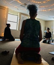 Meg Tipper, founder of the Recovery Community Yoga program and one of its teachers, guides the class in a meditative breathing exercise to facilitate relaxation and start transitioning into a more intentional head space.