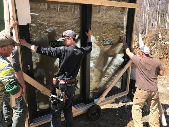 Andrew Dubenetsky (center)  of Shelterwood Construction installs an 800-pound Logic brand lift-and-slide, triple-glazed door.