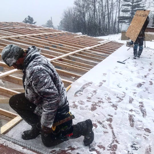 Aron Locker (left) and Charles Wolanin of Shelterwood Construction put down roof sheathing on the company's current project in Fayston.