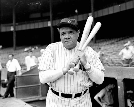 Retired Yankees slugger Babe Ruth warms up with three bats before stepping to the plate at New York's Yankee Stadium, August 21, 1942, as he prepared for a hitting exhibition at the stadium two days later against retired pitching great Walter Johnson.