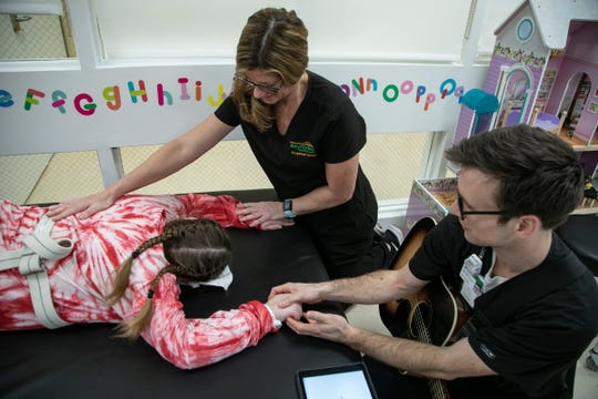 Occupational therapists Jennifer Ancans and music therapist Peter Muszkiewicz stretch Savanah DeHart, 15, as she works through her rehabilitation at the Mary Free Bed Rehabilitation Hospital in Grand Rapids on Thursday, Jan. 23, 2020.