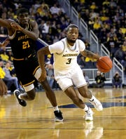 Michigan Wolverines guard Zavier Simpson (3) drives against Appalachian State Mountaineers forward James Lewis Jr. (21) during first half action Tuesday, November 5, 2019 at the Crisler Center in Ann Arbor, Mich.