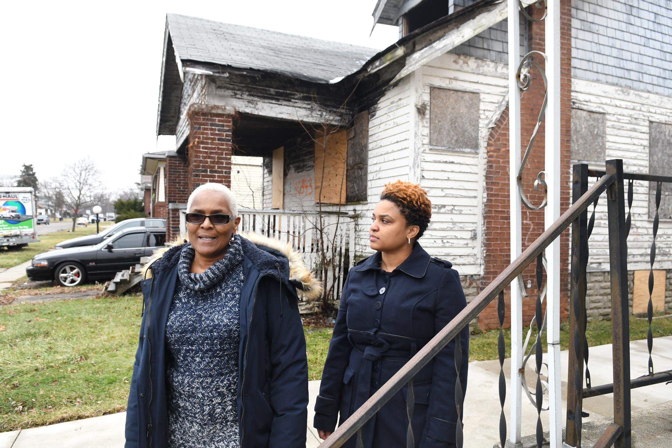 Jackie Smith, left, and her daughter Kellie Smith of Detroit talk about their efforts to have this long-vacant and abandoned house (background) their neighborhood demolished and removed.