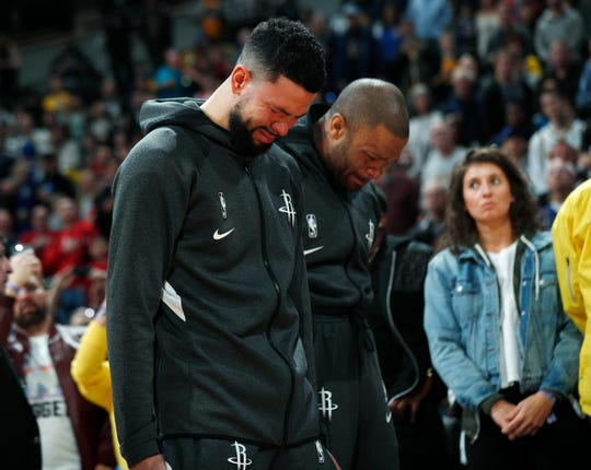 Rockets guard Austin Rivers and forward P.J. Tucker react during a tribute to NBA star Kobe Bryant before Sunday's game against the Nuggets.