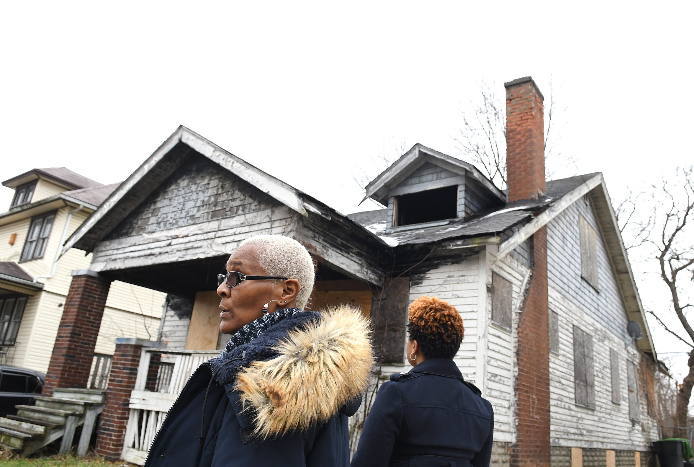 Jackie Smith of Detroit and her daughter, Kellie, look at a neighboring house on their block that has been vacant for years. Jackie has been trying to get the eyesore knocked down and cleared.