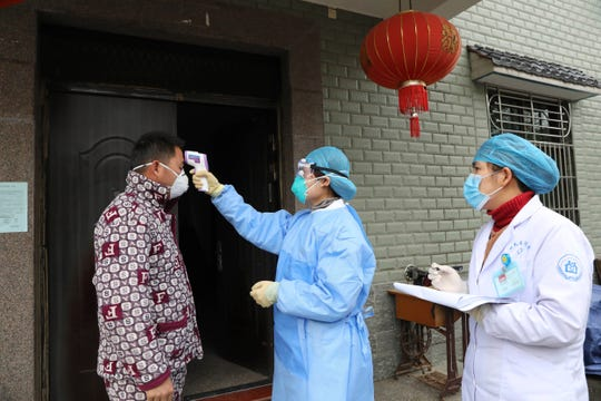 Community health workers check the temperature of a person who recently returned from Hubei Province, center of a virus outbreak, in Hangzhou in eastern China's Zhejiang Province, Monday, Jan. 27, 2020. China on Monday expanded sweeping efforts to contain a viral disease by extending the Lunar New Year holiday to keep the public at home and avoid spreading infection.